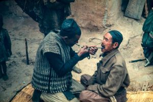 Date: 1970 Locaton: Okhaldunga Description: A blacksmith acts as a dentist to remove a tooth from a porter somewhere on the trail between Okhaldunga and Namche.